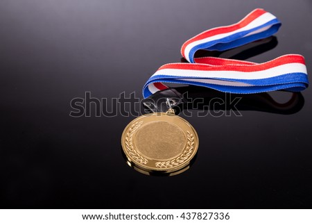 Generic sporting event gold medal with red and blue ribbon on dark background