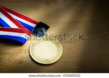 Generic sporting event gold medal with red and blue ribbon on wooden surface against ray of light.  Fine art rendition. - stock photo