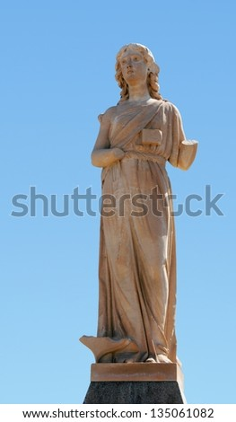 Generic stone figure from the 1920's, damaged by time.  She once held a sword and shield. - stock photo