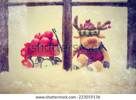 generic stuffed reindeer and holiday decorations with vintage instagram filter and worn window - stock photo