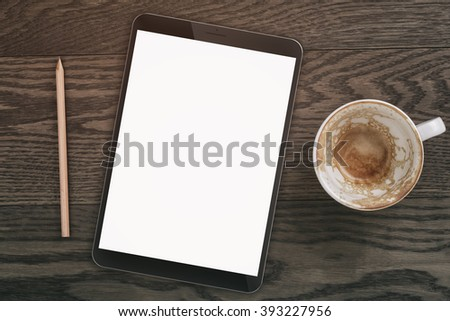 generic tablet pc with blank screen on wood table with empty coffee cup, directly above - stock photo