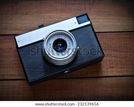 Generic vintage camera on a wooden surface - stock photo