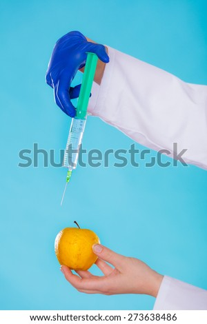 Genetic modification concept. Human hand holding fruit and syginge. Apple receiving an injection of some substance for rapid ripening. - stock photo