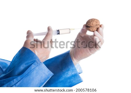 Genetically modified nut and injection in hands of a scientist - stock photo