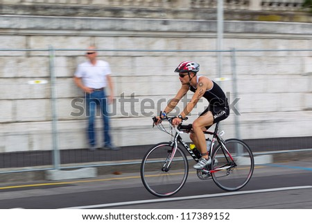 GENEVA - JULY 22: Unidentified athlete competing in the cycling section of the 2012 ITU Triathlon European Cup, July 22, 2012 in Geneva, Switzerland - stock photo
