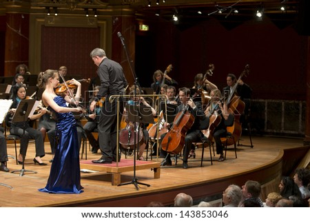 GENEVA - JUNE 23: Soloist violinist Alexandra Conunova Dumortier playing with the United Nations Orchestra conducted by Antoine Marguier at the Victoria Hall June 23, 2013 in Geneva, Switzerland. - stock photo
