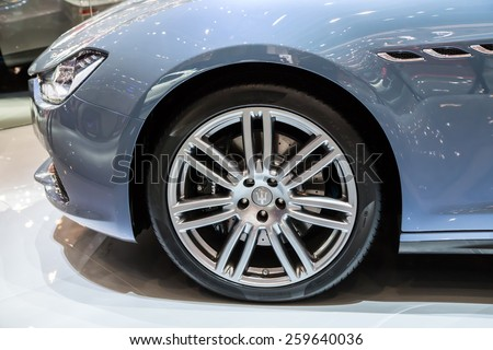 GENEVA, MAR 3: Maserati car wheel and headlight details, presented at the 85th International Motor Show in Geneva, Switzerland on March 3, 2015. - stock photo