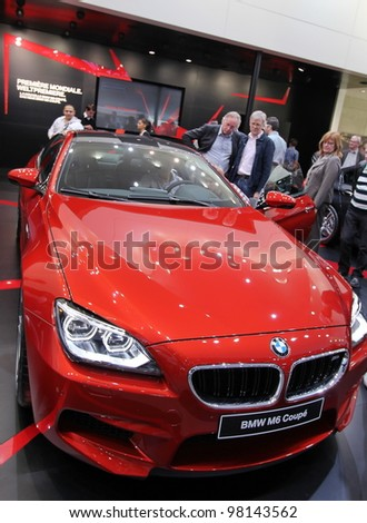 GENEVA - MARCH 16 : Red BMW M6 coupe on display at the 82st International Motor Show Palexpo -Geneva on March 16; 2012 in Geneva, Switzerland. - stock photo