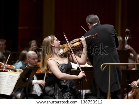 GENEVA -Â?Â? MARCH 20: Soloist violinist, Solenne Paidassi, playing with the United Nations Orchestra conducted by Antoine Marguier at the Victoria Hall March 20, 2013 in Geneva, Switzerland. - stock photo
