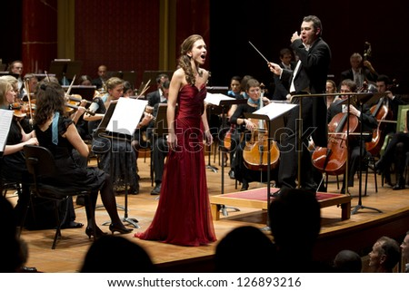 GENEVA - NOVEMBER 17: Conductor Antoine Marguier conducts the United Nations Orchestra and Soprano Alexandra Hewson at the Victoria Hall November 17, 2012 in Geneva, Switzerland. - stock photo