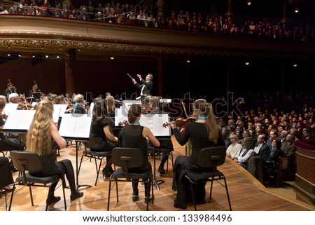 GENEVA - NOVEMBER 17: Conductor Antoine Marguier conducts the United Nations Orchestra at the Victoria Hall November 17, 2012 in Geneva, Switzerland. - stock photo