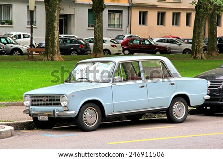 GENEVA, SWITZERLAND - AUGUST 4, 2014: Cyan classical car Fiat 124 at the city street. - stock photo