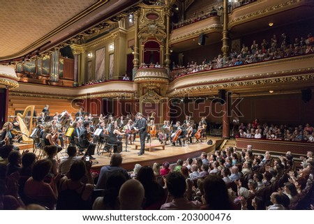 GENEVA, SWITZERLAND - JUNE 22, 2014: Conductor Antoine Marguier presents a bouquet of flowers to the leader of the United Nations Orchestra at the Victoria Hall during a festival of music concert. - stock photo