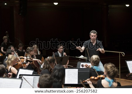 GENEVA, SWITZERLAND - MARCH 21, 2014: Antoine Marguier conducts the UN Orchestra during rehearsals for the Spring Concert 2014 in the Victoria Hall.
