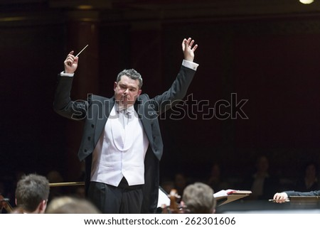 GENEVA, SWITZERLAND  MARCH 1, 2015: Antoine Marguier conducts the United Nations Orchestra at a concert at the Victoria Hall commemorating 200 years of Geneva in the Swiss Confederation. - stock photo