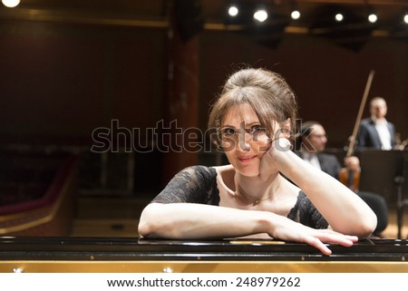 GENEVA, SWITZERLAND MARCH 21, 2014: Pianist Elisso Bolkvadze  poses during rehearsals of the UN Orchestra conducted by Antoine Marguier for the 2014 Spring Concert in the  Victoria Hall. - stock photo