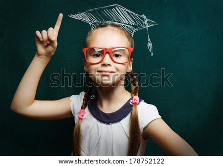 Genius girl in red glasses near blackboard in master hat - stock photo