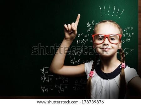 Genius girl in red glasses near blackboard with formulas - stock photo