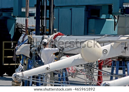 GENOA, ITALY - JUNE 22, 2016: Luxury boats in the marina of Genova Marina Aeroporto (Sestri Ponente). In the picture, a sail shaft is made safe with the aid of mobile crane in Genovesi shipyards.