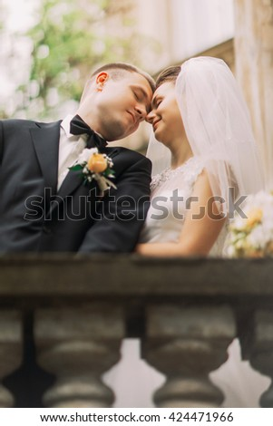 Gentle beautiful bride and groom touching foreheads with closed eyes on the ancient fence balcony, close-up - stock photo