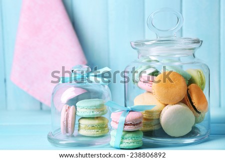 Gentle colorful macaroons in glass jars on color wooden table background