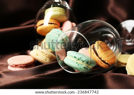Gentle colorful macaroons in wine glass on color fabric background - stock photo