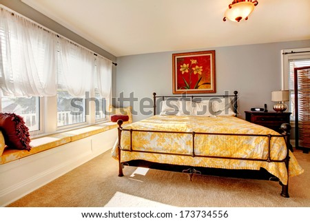 Gentle cozy bedroom with bright white window, yellow bed and beautiful picture on the wall - stock photo