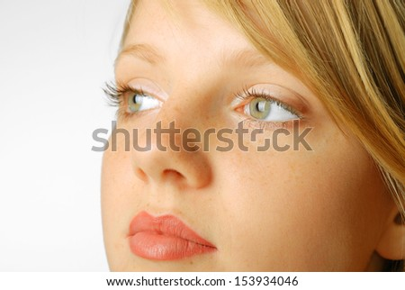 Gentle face of teenage girl is photographed closely isolated on white. Young blonde has smooth skin freckled, full lips and large grey eyes. Copy space is on the left. She is looking sideways.