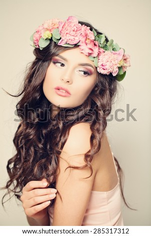 Gentle Floral Portrait of Woman Fashion Model. Curly Hair, Beauty Makeup and Peony Flowers