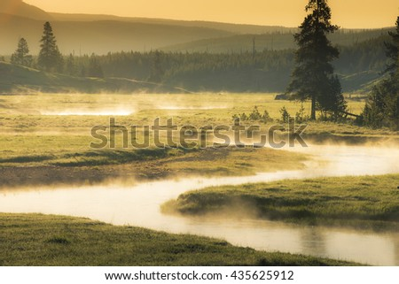 Gentle flowing fishing stream winding through meadow of golden lit summer sky with mist and steam - stock photo