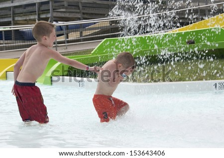 Gentle pushing the brother pushes his sibling into the spray on a hot summer day - stock photo