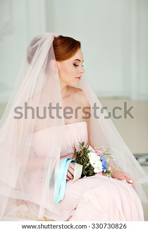 Gentle, sensual portrait of very beautiful girls bride blonde in a pink dress and veil with a bouquet of flowers in his hands, a bright interior