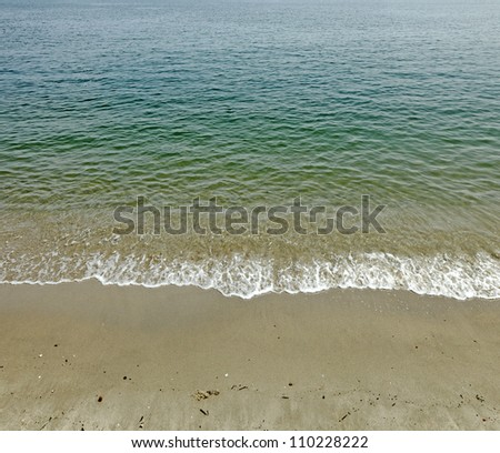 Gentle shallow wave rolling onto a sandy beach from a turquoise sea. - stock photo