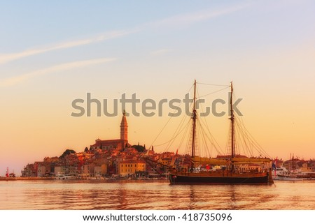 Gentle sunrise over the Adriatic sea and town - panoramic view of the peninsula and a sea boat, Rovinj, Croatia - stock photo