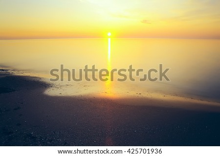gentle sunrise over the sea. the sun rises above the horizon. Quiet motionless expanse of water, gentle paint.  - stock photo