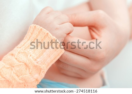 Gentle touch. Mother holding gently the hand of her baby  - stock photo