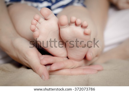 Gentle touch. Woman holding tiny baby feet in her hands - stock photo