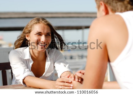 Gentle Touching Hands: Young happy smiling romantic couple man and woman holding hands and sitting outdoors on cafe terrace by the sea