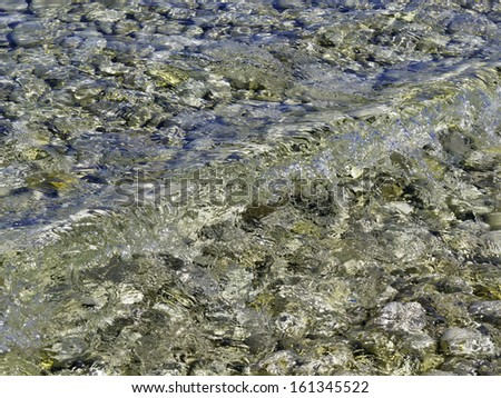Gentle wave above rocks from the last Ice Age in shallows along Lake Michigan, Door County, Wisconsin - stock photo