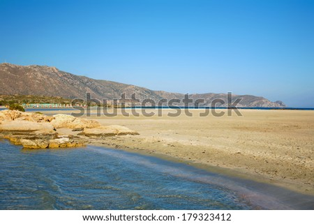 Gentle waves lap Elafonissos beach on the south-west coast of Crete, Greece, washing pink sand from crushed sea urchins onto the strandline. - stock photo