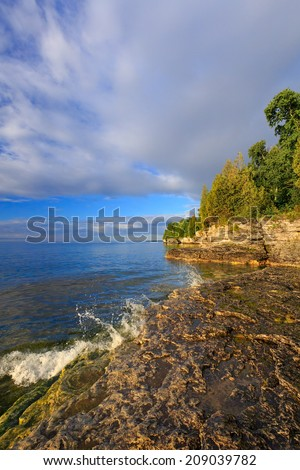 Gentle waves splash on the rocky shoreline of Door County, Wisconsin's Cave Point. - stock photo