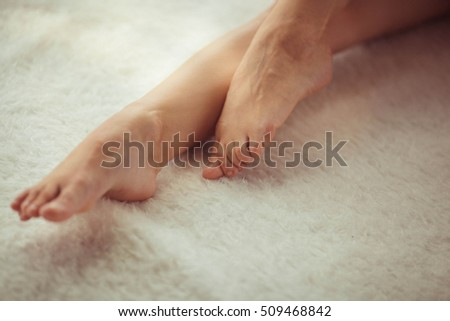gentle woman's foot on the soft white coverlet