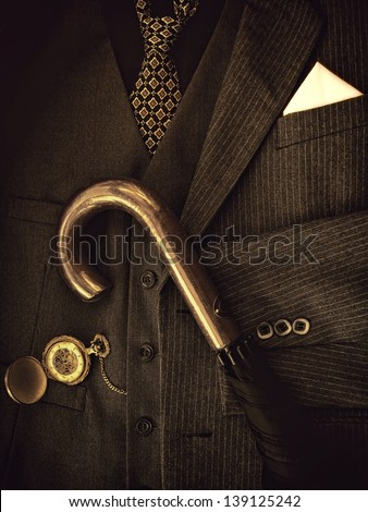 Gentleman's suit with pocket watch and umbrella.Sepia image. - stock photo