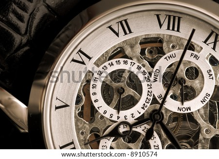 Gentleman's watch, with exposed mechanism showing wheels and cogs - stock photo