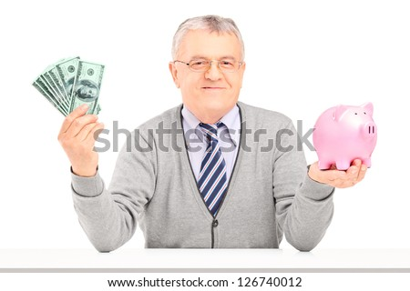 Gentleman sitting, holding a piggy bank and US dollars isolated on white background - stock photo