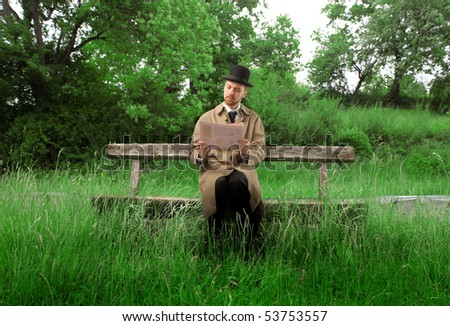 Gentleman sitting on a park bench and reading a newspaper - stock photo