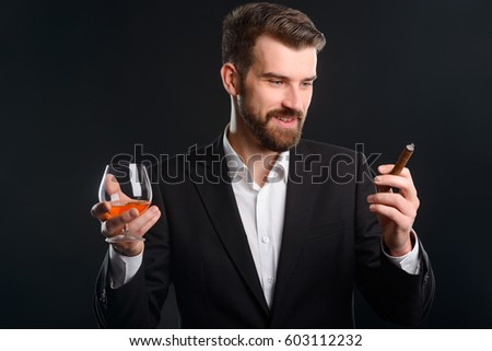 Gentleman with glass and cigar. Portrait of a bearded man in stylish clothes: white shirt under black club jacket. He's holding a glass of premium brandy in one hand and expensive cigar in another.