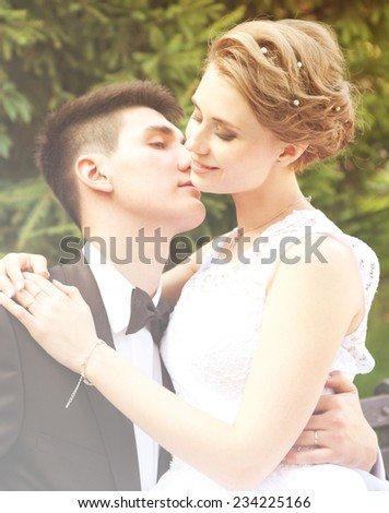 gently groom kisses the bride, wedding day, image with soft focus with sunshine glares
