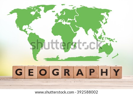 Geography sign with a world map on a wooden desk - stock photo