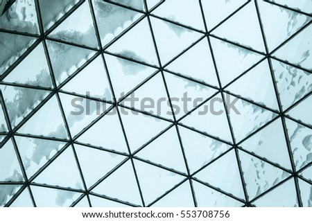 Geometrical shapes on the glass roof with snow on her shopping center